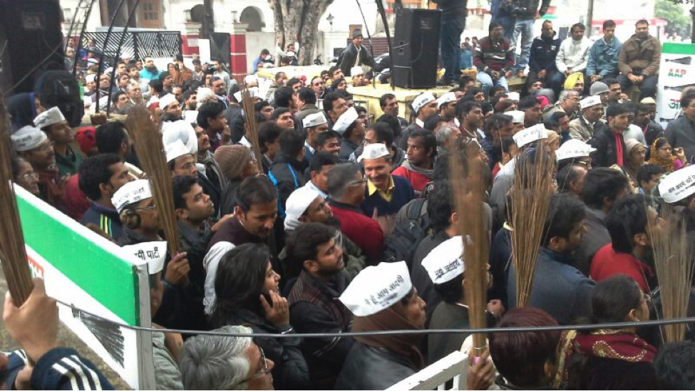 AAP supporters wearing the party cap and holding up brooms, their election symbol. Photo: Yotsana Tripathi